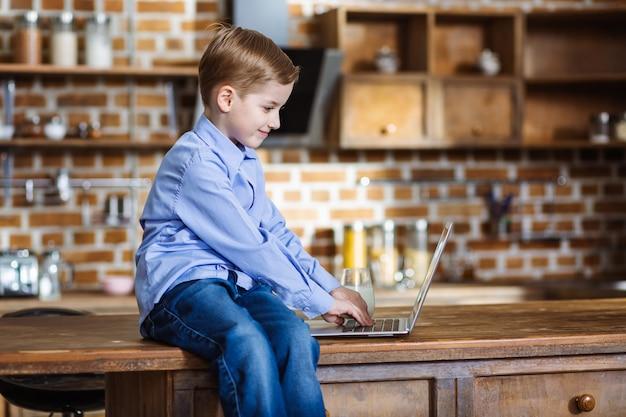 Cheeful petit garçon à l'aide de son ordinateur portable assis sur la table