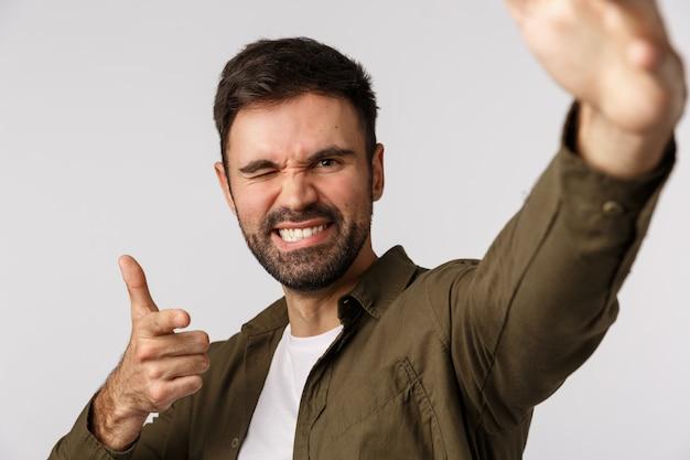 Cheeky et insouciant confiant beau mec barbu, prenant selfie comme tenant le smartphone d'une main, faisant un geste de pointage comme vérifiant quelqu'un, parlant un appel vidéo et félicitant un ami, clin d'œil