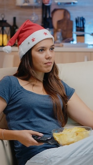 Cheerful adult wearing santa hat et regarder la télévision