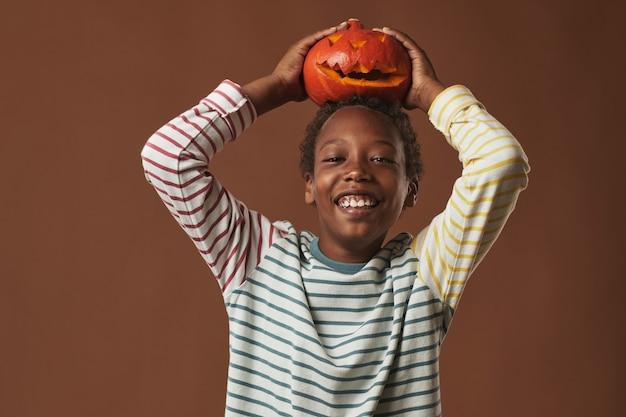 Cheerful african american boy portant une chemise à manches longues rayée tenant jack o 'lantern sur sa tête souriant à la caméra, portrait en studio