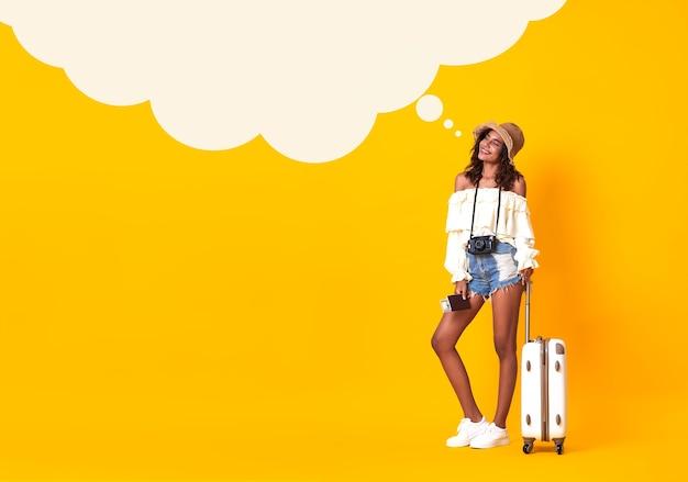 Cheerful african woman holding passeport avec billet à la recherche de bulle vide sur jaune.