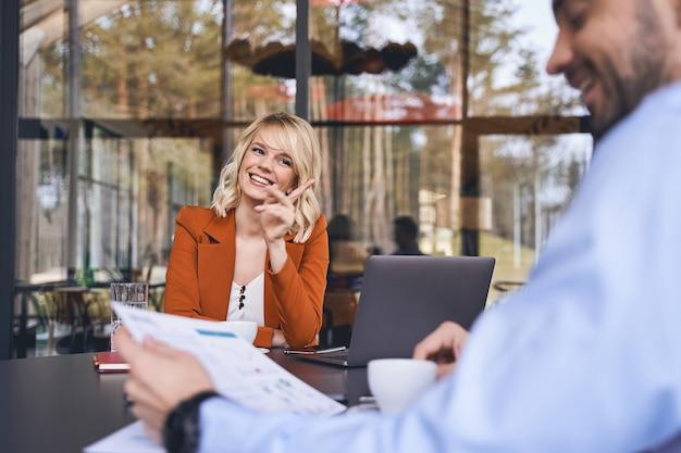 Cheerful belle élégante jeune femme entrepreneur caucasien assis devant son collègue masculin souriant