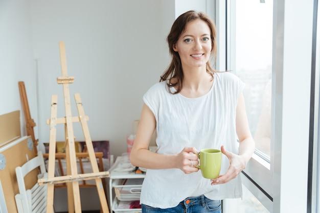 Cheerful belle femme peintre buvant du thé près de la fenêtre dans un studio d'art
