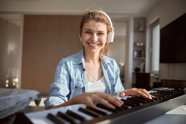Cheerful brunette gardant le sourire sur son visage tout en regardant directement la caméra