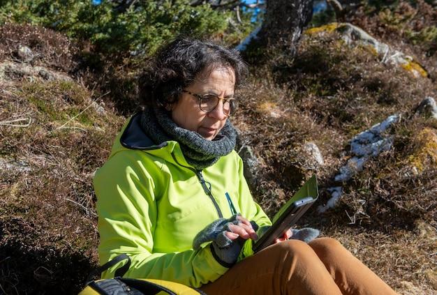 Cheerful brunette senior woman using smartphone outdoors