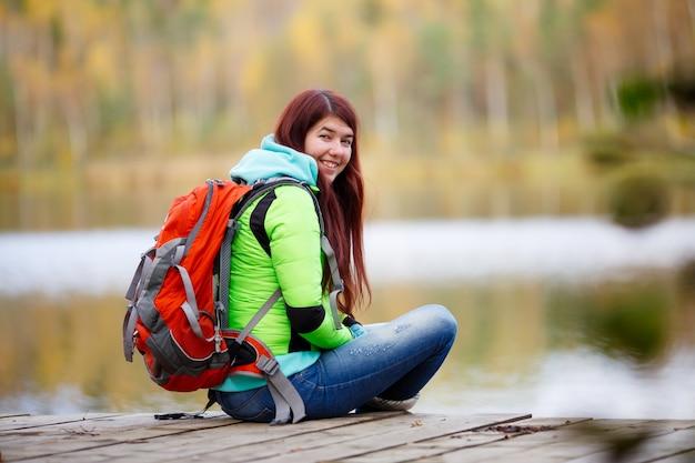 Cheerful brunette sitting avec sac à dos au lac