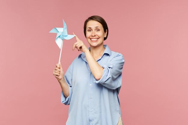 Cheerful brunette woman in blue shirt jouant avec du papier whirligig