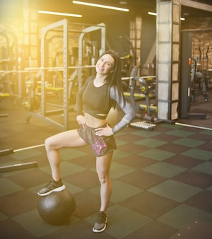 Cheerful brunette woman in sportswear avec médecine-ball posant à la caméra dans la salle de gym.