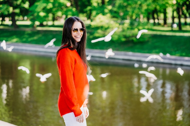 Cheerful brunette woman in sunglasses habillé en pull rouge et pantalon blanc marchant parmi la rivière