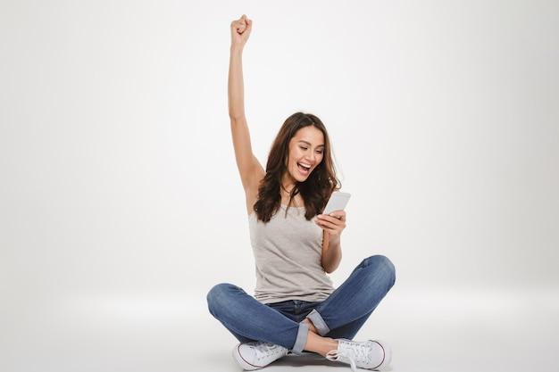 Cheerful brunette woman sitting on the floor et se réjouit lors de l'utilisation de smartphone sur gris