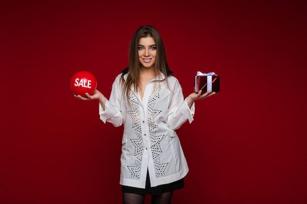 Cheerful caucasian woman avec ballon rouge avec vente sur elle d'une part et petite boîte rouge avec un cadeau de l'autre