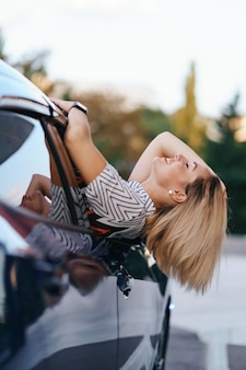 Cheerful caucasian woman conduit à travers la pittoresque ville ensoleillée et agite ses bras tout en s'étirant par la fenêtre de la voiture par une belle journée