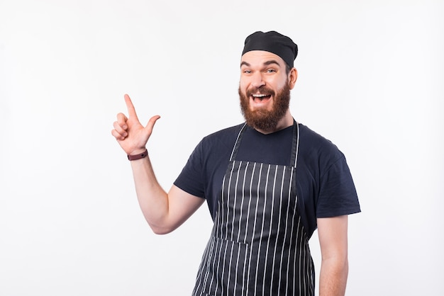 Cheerful chef homme avec barbe pointant vers copyspace