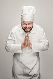 Cheerful chef joignant les mains de gratitude