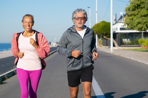 Cheerful couple d'âge mûr qui longe la rive du fleuve. homme et femme aux cheveux gris portant des vêtements de sport, jogging à l'extérieur. concept de mode de vie actif et d'âge