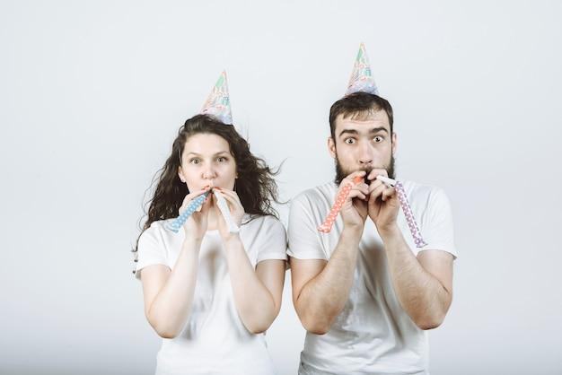 Cheerful couple homme et femme en casquettes de fête dans une corne sur fond gris