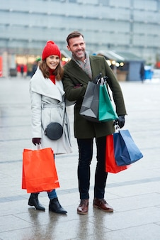 Cheerful couple shopping à l'extérieur ensemble