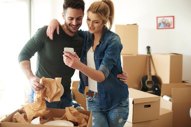 Cheerful couple using phone lors d'un déménagement