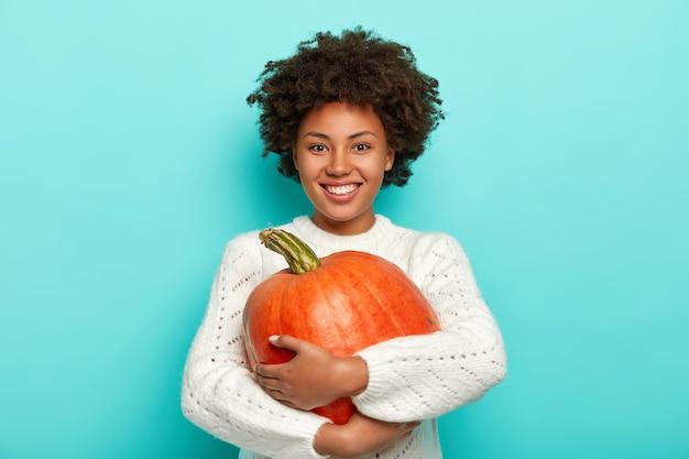 Cheerful curly woman embrasse la citrouille mûre, sourit agréablement, vêtue d'un pull blanc