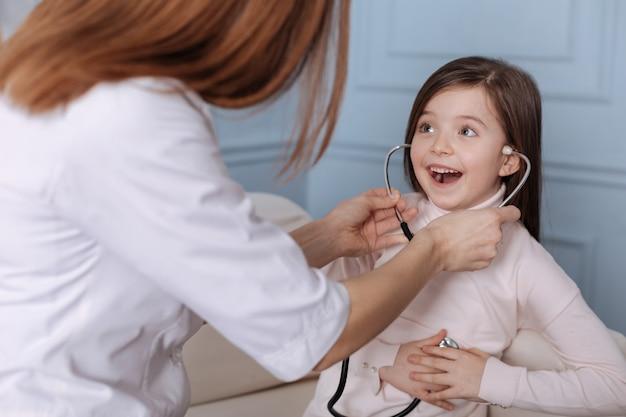 Cheerful cute little girl holdign stéthoscope et assis sur le canapé avec un médecin professionnel tout en exprimant sa joie