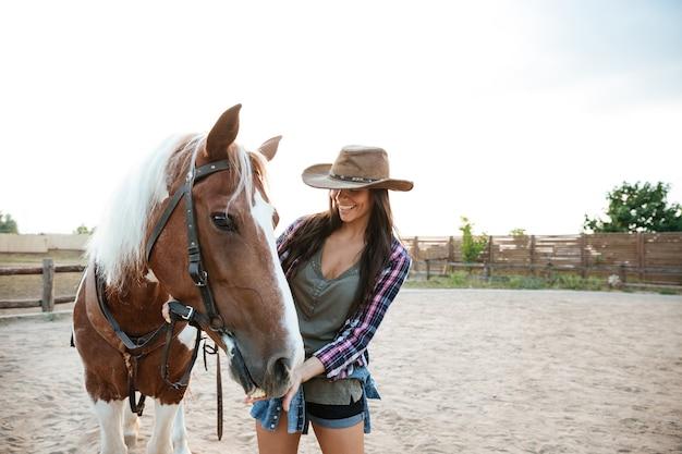 Cheerful cute young woman cowgirl debout et prenant soin de son cheval dans le village