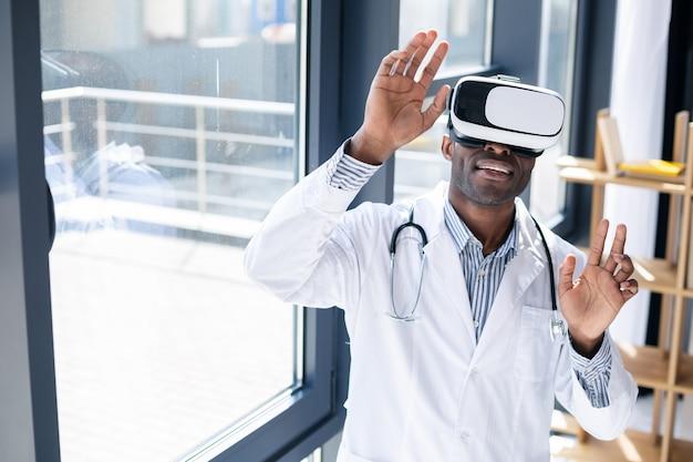 Cheerful doctor portant l'uniforme et jouant avec un gadget portable