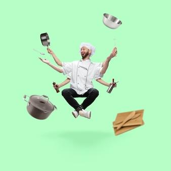 Cheerful émotionnel beau cuisinier chef boulanger à plusieurs bras en lévitation isolé sur vert
