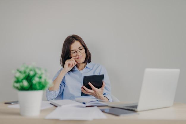 Cheerful female financial manager tient la calculatrice dans les mains, étant satisfait