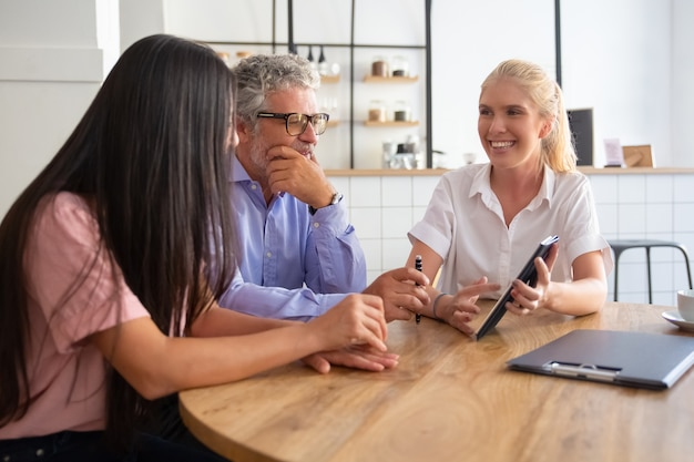Cheerful female manager et clients jeunes et matures regardant et discutant de la présentation sur tablette, souriant et parlant
