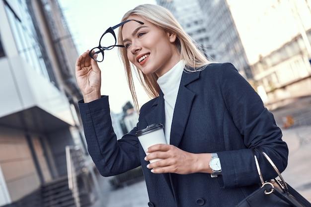 Cheerful female manager se rendre au travail à pied en buvant le matin