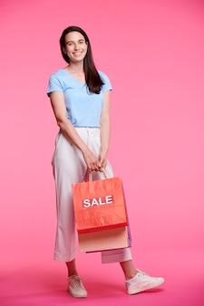 Cheerful female shopper en tenue décontractée transportant des tas de sacs en papier après un shopping réussi