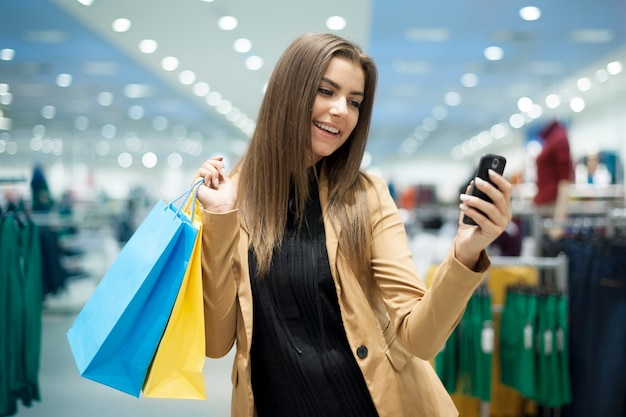 Cheerful female shopper textos sur téléphone mobile