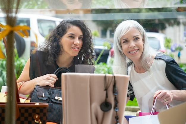 Cheerful female shoppers fixant les accessoires dans la vitrine, tenant des sacs à provisions, debout au magasin à l'extérieur. vue de face à travers le verre. concept de magasinage de fenêtre