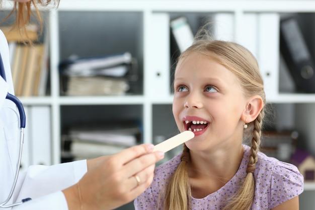 Cheerful girl en cours d'examen chez une femme médecin