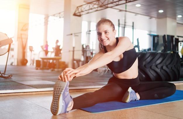 Cheerful girl faisant étirement ses jambes avant de s'entraîner assis sur un tapis dans la salle de gym entraînement pré-entraînement