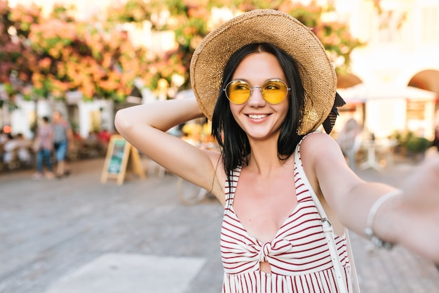 Cheerful girl holding hat tout en faisant selfie et rire des amis en attente sur la place principale de la ville