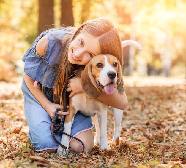 Cheerful girl hugging dog beagle à l'extérieur