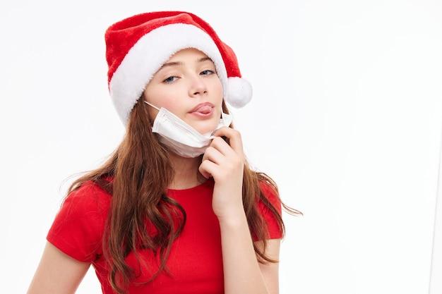 Cheerful girl montrant la langue masque médical fond clair de nouvel an. photo de haute qualité