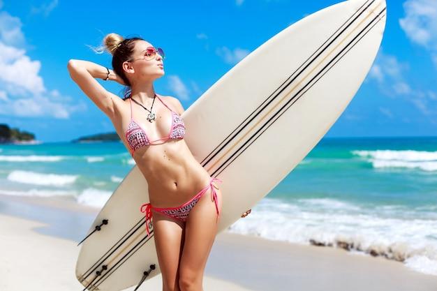 Cheerful girl posant avec planche de surf