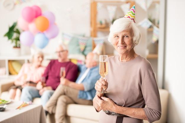 Cheerful grand-mère en chapeau d'anniversaire tenant flûte de champagne