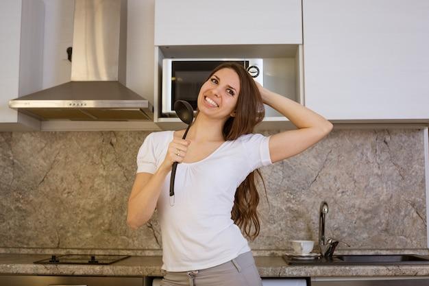 Cheerful happy woman chant dans la cuisine avec une louche à la main