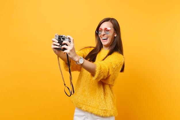 Cheerful happy young woman in heart lunettes faisant prise de selfie sur appareil photo vintage rétro isolé sur fond jaune vif. concept de mode de vie des émotions sincères des gens. espace publicitaire.