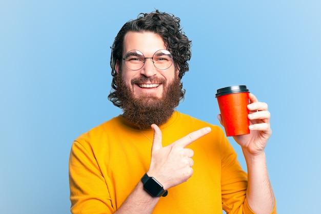 Cheerful hipster barbu homme pointant sur une tasse de café à emporter