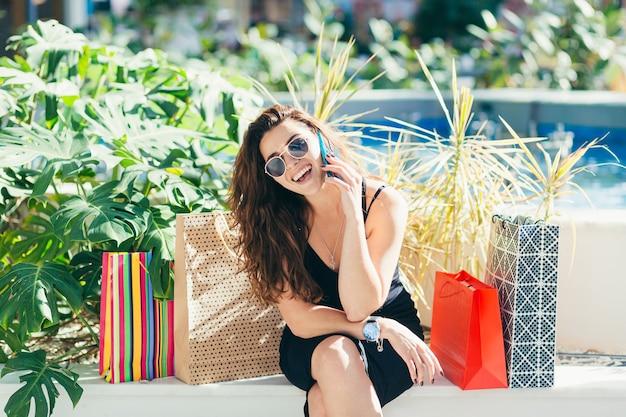 Cheerful lady en élégante robe noire portant des sacs colorés tout en marchant au magasin