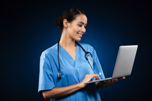 Cheerful lady in medical uniform using laptop