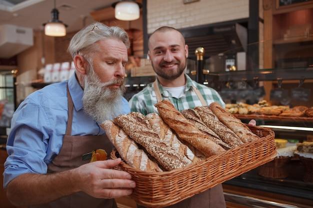 Cheerful male baker montrant son père du pain frais dans un panier