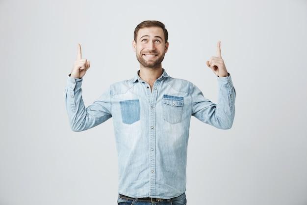 Cheerful male avec barbe à la recherche et pointant vers le haut à la publicité
