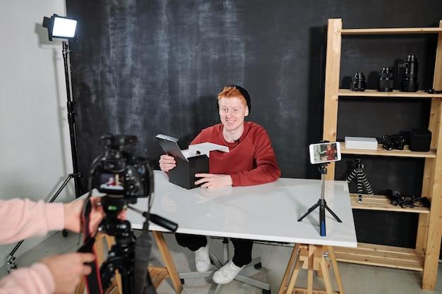 Cheerful male vlogger par 24 va déballer la boîte avec une nouvelle photocamera pendant le tournage vidéo en studio