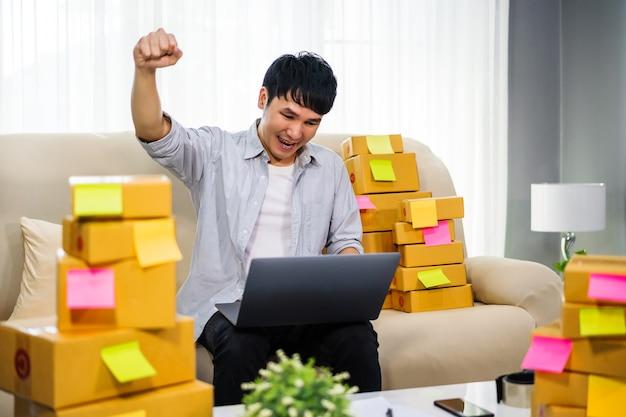 Cheerful man entrepreneur travaillant avec un ordinateur portable et succès de la vente de produits en ligne au bureau à domicile