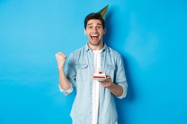Cheerful man looking happy, célébrant l'anniversaire en chapeau de fête, tenant le gâteau b-day et faire la pompe de poing, debout sur le mur bleu
